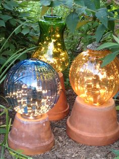 Garden lights made from flower pots and old lamp globes with strings of white lights in the globes.