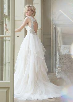 Vestido de novia corte princesa con cut outs en la espalda; falda confeccionada con tul y cauda larga - Foto Hailey Paige en JLM Couture