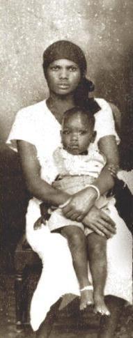 Habiba Akumu Obama, President Barack Obama's paternal grandmother, and his father, Barack Obama, Sr., is seated on Habiba's lap.