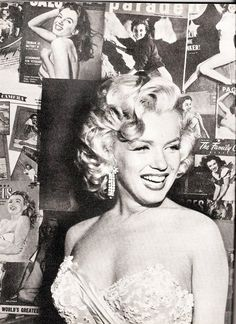 Marilyn Monroe stands in front of a wall covered by vintage magazine covers of herself.