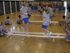 TINIKLING in PE in high school.  :-)  It is a folkdance with sticks, imitating the movement of a bird called the Tikling.  We would do the steps to song.