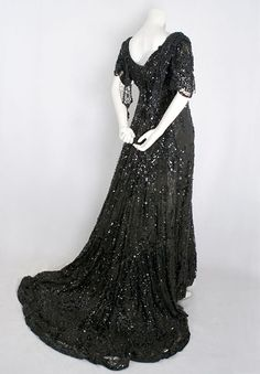 "Beaded tulle evening gown, c.1910. In this scintillating evening gown, we see the opulent elegance of the Gilded Age materialized in the world of high fashion. The textured black-on-black design adds a layer of glamour to the languid elegance of the late Edwardian period. Label reads ""J.L. Conley/Boston."""