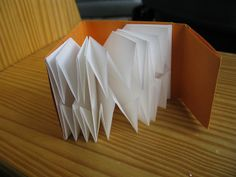 Exploding Map Fold Book w/ Cover. Series of expanding map folds that collapse & are held together w/ cover tab closure. Folded from strip of paper w/ proportions of 3:8, ends up square. Starts as a 8-panel accordion fold (height of each panel is 3x its width. Outer 2 panels are for cover attachment & inner 6 panels fold into 3 maps. Light Impressions Apollo Lightweight, French Paper Company Dur-O-Tone Butcher Orange, 60 lb. Text.