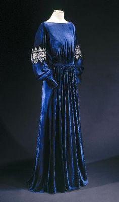 Blue velvet dress with bateau neckline, bishop sleeves, full skirt, and silver detailing (embroidery?) at sleeve mid-point. By Jeanne Lanvin in 1935.  Musée Galleira de la Mode de la Ville de Paris