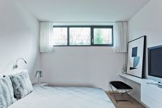 small white bedroom interior with study nook and tv stand
