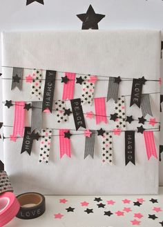 White kraft paper gift wrap with neon pink, black and white washi tape flags banner and paper punched little stars banner sewn together with a sowing machine. From mamas kram.