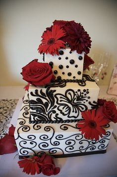 Black & White Wedding cake:  Square Tiers with black scroll work, Black polka dots black artwork and red flowers
