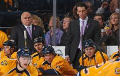 Head coach Barry Trotz and assistant coach Lane Lambert of the Nashville Predators wear lavender ties and ribbons during the #HockeyFightsCancer night.