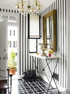 A white Roman shade bordered in black adds more graphic punch to the foyer.