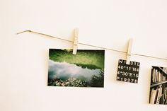 use twine, attach it from two screws inserted in the wall and attach the photos using clothespins.