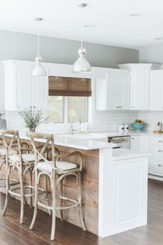 A gorgeous, bright white kitchen by Deluxe Design Studio! The white counters, subway tiled backsplash, and French cafe counter stools make us #HomeGoodsHappy