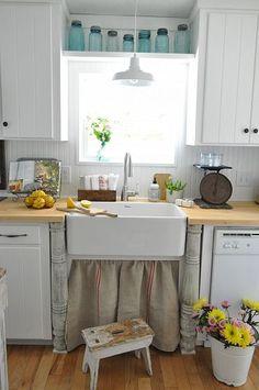 Farmhouse kitchen with vintage columns, grain sack sink skirt, and mason jars.