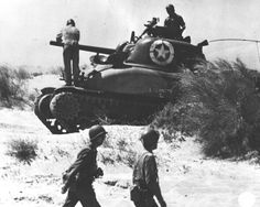 Crew of US M4 Sherman tank 'Eternity' checking the tank after landing at Red Beach 2, Sicily, 10 Jul 1943 (US Army Signal Corps)