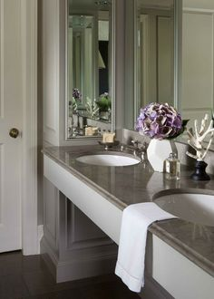 Mirrored walls make a space seem larger.      Formal millwork and silver-framed mirrors reflect '30s-era elegance in Calgary designer Nam Dang-Mitchell's principal bathroom. Both counters and floor are finished in cool grey limestone for a luxurious feel.