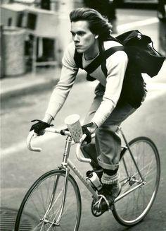 Kevin Bacon rides a bike.
