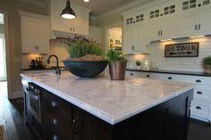 White kitchen, brick backsplash, black island with marble counter? New England Homes