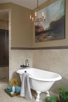 This claw-foot tub is set for zoning out with the focal mood lighting of a vintage-look chandelier, and gaze-worthy tan tile wainscot. | Photo: Nathan Kirkman