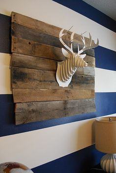 "cardboard deer head ""mounted"" to upcycled wooden palette pieces."