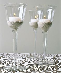Place a votive candle in a glass anchored in a bed of sand or small pebbles and Voila!  Lighting that goes with your tableware.
