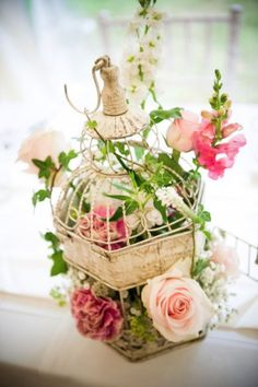 english country garden meets shabby chic with roses arranged in bird cages