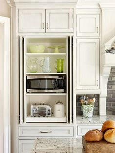 hidden microwave and appliance pantry. backsplash.