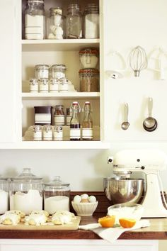 Organized kitchen cabinet with glass jars and bottles.