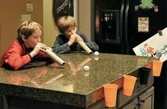 Tape a cup to the end of a table & have them blow ping pong balls in them with paper towel rolls.