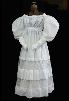 Romantic period cotton dress, circa 1830. Made from white cotton with inserts of embroidered net lace, dainty pleated bodice, and exaggerated gigot sleeves. They first appeared around 1830, making the waist appear smaller and emphasizing female curves. The emblematic full gigot sleeves have long narrow, ruched cuffs. The ruching is held in place with narrow bands of lace outlined with corded piping. The sleeves close with tiny thread-covered buttons.