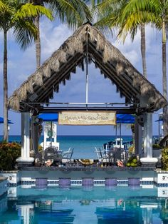 Relax poolside at a beach side bar at the Grand Cayman Beach Suites. #CaymanIslands