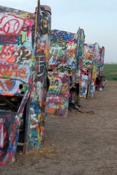 Cadillac Ranch. An art installation of 10 Cadillac cars half buried, spray painted, welcoming spray painting from those visiting the installation.  Amarillo TX