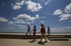 Christine Hadley walks on the boardwalk at Buckroe Beach with her three daughters, from left, Bella, 7, Catherine, 10, and Diana, 5, on Monday. As a part of an action plan developed during a diabetes self-management class, Hadley walks on the beach several times a week to maintain her fitness. (Photo by Kaitlin McKeown/Daily Press)