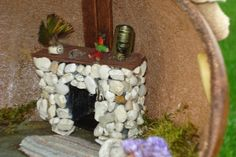 Gourd Fairy House Fireplace interior. This fireplace made with a cigarette pack cut down and colored black.  Then I used a hot glue gun to add color sorted pea gravel. The mantle is a bar coaster colored brown with a sharpie. Such Fun!