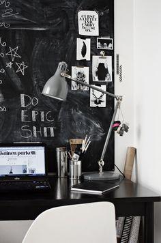 chalkboard wall behind desk.