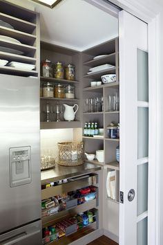 Amazing taupe kitchen walk-in pantry with open shelving and pull-out snack drawers. Stainless steel countertop, subway tile backsplash and frosted pocket doors!