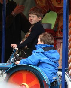 James, Viscount Severn (L), son of Prince Edward, Earl of Wessex, and Sophie, Countess of Wessex, rides on the fun fair carousel on day 4 of the Royal Windsor Horse Show