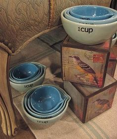 make a couple of pretty wood boxes into display by collaging paper onto them.  Use old kleenex boxes?  Could make in any color to match decor of the booth, and offers height variations