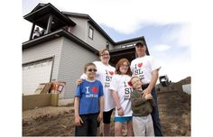 The Kebel family stands in front of their new home that they just received the keys to on May 15, 2012 in Slave Lake, Alberta.