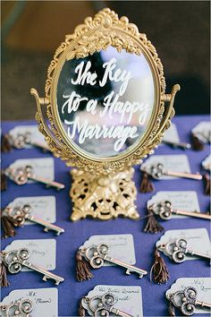 "Such a cute idea! ""The key to a happy marriage"" written on an elegant gold mirror with escort cards attached to decorative keys."