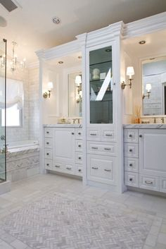 Ensuite bathroom design with custom built white bathroom vanities & cabinet with marble counter tops, marble tiles floor in a herringbone pattern, marble subway tiles bath & shower surround and lucite acrylic chandelier.