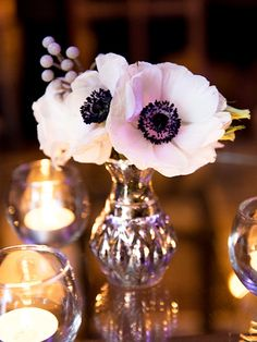 Silver bud vases filled with white anemones and grey dusty miller and silver mercury glass votives will accent the cocktail tables