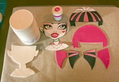Prepare white and Fuchsia sugar paste and  cut out hair, face and earrings. by cutesweetthings