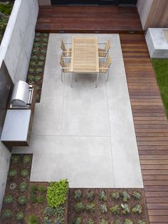 The juxtaposition of the smooth concrete, wood and the rows of plants is calming, relaxing and perfectly modern.