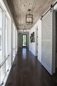 interior design, the doors, ceiling lighting, floor, light fixtures, sliding barn doors, wood ceilings, hallway, sliding doors
