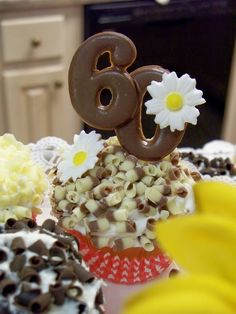 Close up of the guest of honor's cupcake topped with a chocolate molded '60' and flower detail.