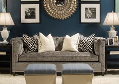 Dark blue walls, black and white accents, Gray couch.