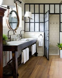 I love everything about this rustic bathroom, especially the salvaged wood vanity and the shower door.