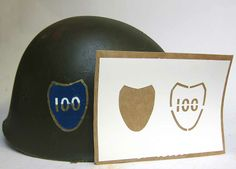 Apply the blank shield first and paint in blue. Allow to dry and then apply the '100' stencil making sure the edges surround the blue shield properly. Paint in the outline and the bottom half of the '100' in gold or yellow paint and allow to dry. Paint in the top half of the '100' in white paint and allow to dry. Remove the stencil and hand paint in the sections where the 'tabs' were, including joining up the gaps in the '100'. www.warhats.com
