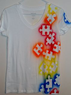 Lay down big puzzle pieces and spray paint over them. Wait until they dry to take the off. - autism awareness! @Julie Marriott
