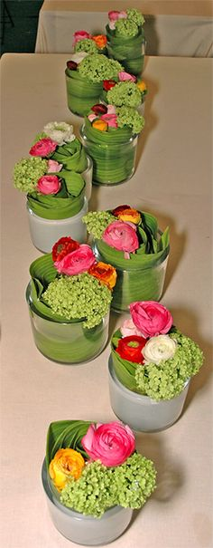 """Bring more flowers into life; these look quite easy for table decorations. Every glass contains water and an Aspidistra tricolor leave rolled up which sustains flowers of Ranunculus and Viburnum opulus """"Roseum""""."""