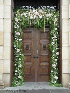 Wedding Flowers - Doorway adorned with lush garland makes a welcoming entrance for bride and groom.